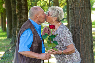 Mature senior couple is in love. Man hands over a rose.