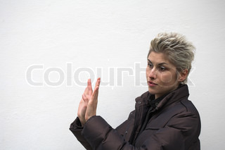 pretty woman outdoor with hands in sign of refusing, white wall as background