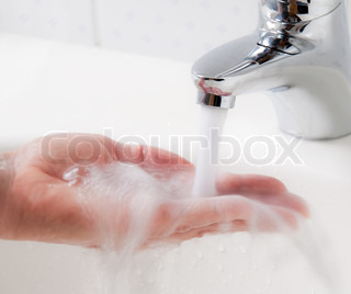 Woman washes with running water and soap hands. Protection from infection of the new flu H1N1.