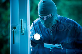 A burglar at a window of a house.