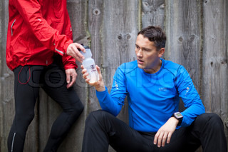 Man is drinking water after jogging