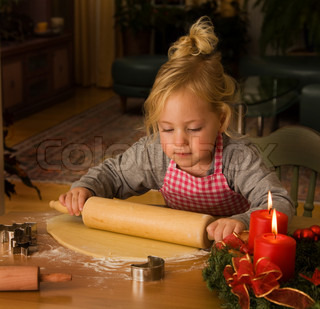 Child baking Christmas cookies during Advent