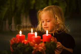 Child with Advent wreath for Christmas. 4 candles lit.