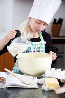 A young girl pouring milk into a bowl