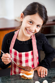 A smiling girl decorating a Easter bun with melted chocolate