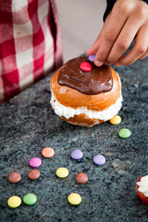 A girl decorating a Easter bun with melted chocolate