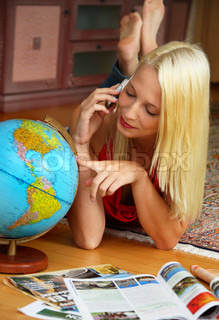 Young woman leafing through travel brochures with a globe.