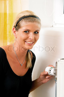 Woman with radiator. Save energy. Thermostat of the heater. Save on heating costs.