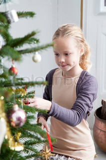 A young caucasian girl decorating the Christmas tree