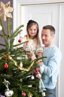 A father and his daughter decorating the Christmas tree
