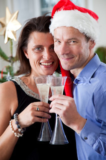 A caucasian couple celebrating Christmas with champagne