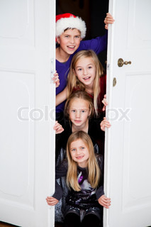 A group of caucasian children opening a door on Christmas day