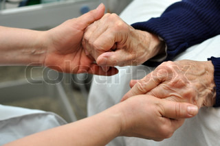Anurse taking hands of an old woman