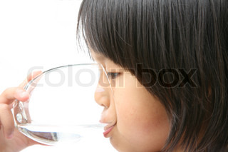 child drinking a glass of water on white background