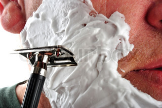 one wet shaving razor and some foam in a face
