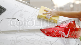 Woman Washing a car with a sponge and soap.