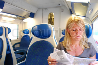 Mid adult woman reading map in train