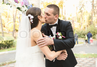 portrait of happy bride and groom kissing first time at ceremony