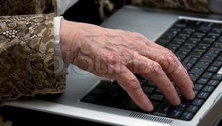 hand of a woman older then 80 , working on a mobile laptop
