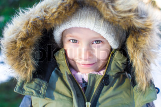 Portrait of little happy girl in snow sunny winter day