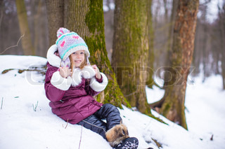 Portrait of little happy girl in the snow sunny winter day