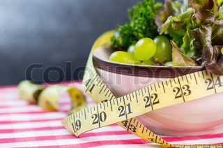Diet green salad and measuring tape slimming