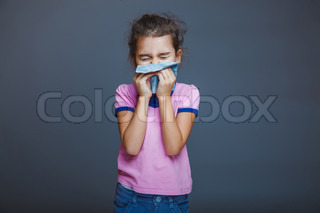 girl child sneezes into  handkerchief on a gray background