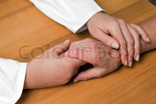 the hands of a senior citizens held by the hand of a nurse