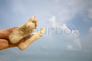 The feet of a woman lying on the sand beach. Rest and relax on vacation.