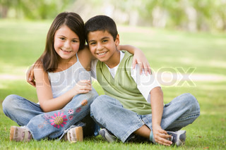 Two children sitting in park together
