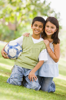 Two children playing football in park looking to camera