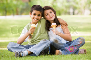 Two children eating icde cream in park looking to camera