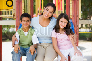 Mother and children in playground sitting on climbing frame