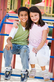 Two children in playground on climbing frame
