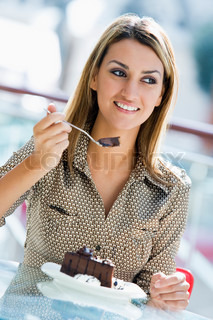 Woman sitting in cafe enjoying chocolate cake