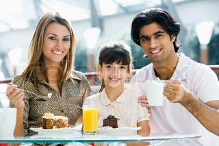 Family eating cake in cafe looking to camera