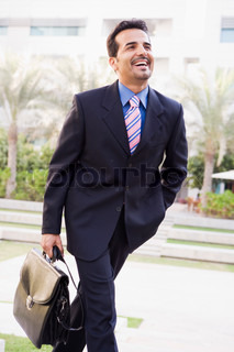 Businessman walking to office carrying briefcase