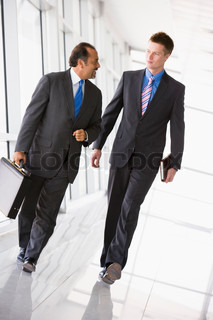 Businessmen walking through office lobby