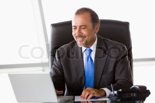 Businessman working at laptop in office