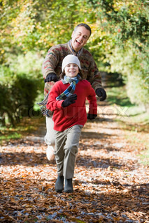 Grandfather and grandson running through autumn woods