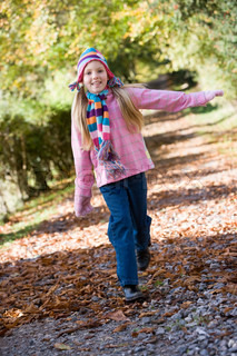 Young girl playing in autumn woods