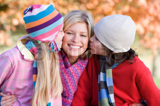 Children giving mother kiss on autumn walk