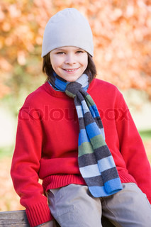Young boy sitting on fence against autumn foliage