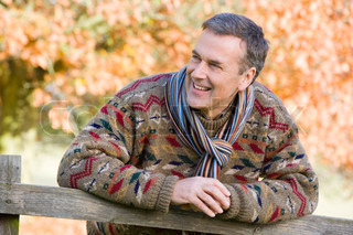 Senior man resting on fence with autumn leaves in background