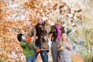 Far kaster efterårsblade i luften