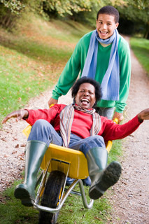 Son pushing laughing mother in wheelbarrow