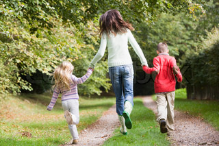 Mother and children running along autumn path in woodlands