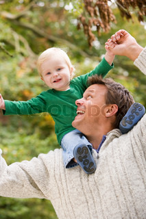 Father giving young son ride on shoulders outside