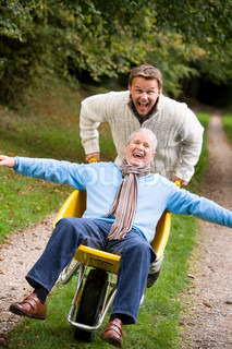 Grown up son pushing father in wheelbarrow along autumn path