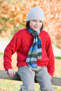 Young boy sitting on fence with autumn woods in background
